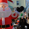 """Danvers:<br /> Tayla Camara 8, left, and her sister Sabrina Camara, 11,  look toward the inflatable Santa in their front yard. Lisa and John Camara's holiday display sports five inflatables, candy canes, three Christmas trees, Santa on his sleigh on the lawn and Santa sliding down the chimney on the roof.  There's a five-in-one inflatable feature a band that plays music. """"Every year, I add more and more,"""" said Lisa Camara, who said people driving by stop when they see the display. She estimates the family spends an extra $200 on electricity, and the scene is a delight to her kids, Sabrina and Tayla.<br /> Photo by Ken Yuszkus/Salem News, Monday December 8, 2008."""