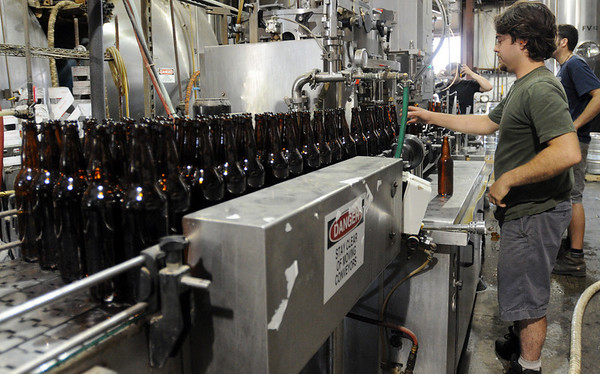 Ipswich:<br /> Michael Higgins works at the 22ounce bottle filler machine at the Ipswich Ale Brewery.<br /> Photo by Ken Yuszkus/Salem News, Friday, June 11, 2010.