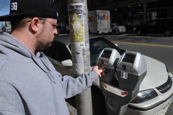 "Salem:<br /> Matthew Bernier places quarters into the new meter on Washington Street in Salem. Salem has 50 new ""smart"" parking meters downtown that accept credit cards. <br /> Photo by Ken Yuszkus/Salem News, Tuesday,  March 6, 2012."