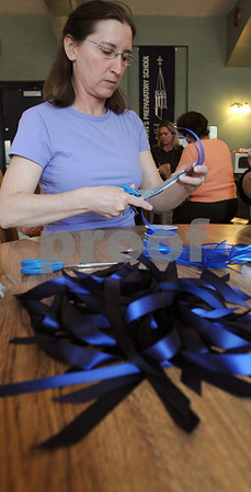 Danvers:<br /> Debbie Wilson of Danvers, cuts ribbon to make remembrance ribbons at St. John's Prep, Memorial Dining Hall. A group of parents gathered to make remembrance ribbons for the Bekels, the father and son who died in a car crash.<br /> Photo by Ken Yuszkus/Salem News, Tuesday May 12, 2009.