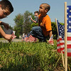 Peabody:<br /> Matthew Dalton, left, and Joseph Denton, both 2nd graders, place flags on the lawn in front of the John E. McCarthy School in Peabody at the conclusion of the school's Memorial Day ceremonies on Friday morning. Approximately, 250 small flags were placed in front of the school by all the students.<br /> Photo by Ken Yuszkus/Salem News, Friday, May 27, 2011.