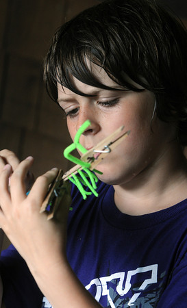 Marblehead:<br /> Calder Mazel, 10, creates a centipede out pipe cleaners and wooden sticks during an activity at the day camp at Hammond Nature Center in Marblehead.<br /> Photo by Ken Yuszkus/Salem News, Monday, July 16,  2012.