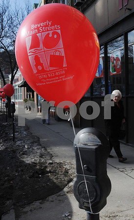 """Beverly:<br /> Hilde Janard of Salem, walks by one of the many balloons attached to the parking meters on Cabot Street. The Promotions Committee tied a red balloon on every parking meter on Rantoul and Cabot Streets and along other streets in the downtown area as part of the """"Painting the Town Red"""" promotion to remind everyone that downtown Beverly is a great place to celebrate Valentine's Day!<br /> Photo by Ken Yuszkus/Salem News, Friday,  February 13, 2009."""