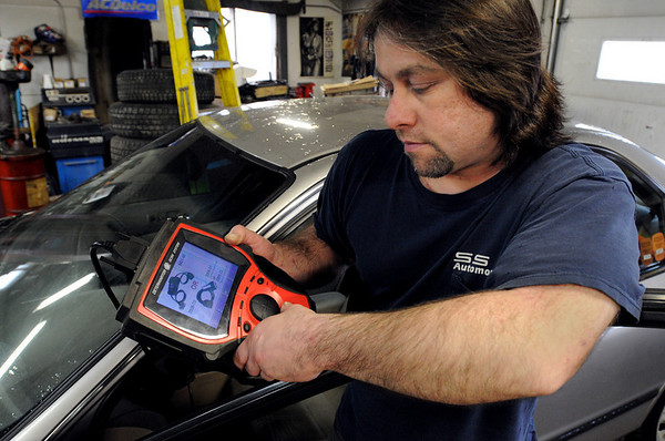 Salem:<br /> Jim Sully, of SS Automotive, works with a scanner plugged into an automobile at the garage.<br /> Photo by Ken Yuszkus/Salem News, Thursday, March 4, 2010.