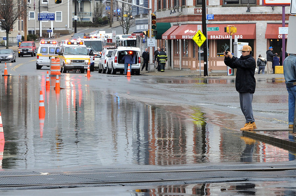 Peabody:<br /> A pedestrian takes photos of the high water on Central Street in Peabody Square.<br /> Photo by Ken Yuszkus/Salem News, Wednesday, March 31, 2010.