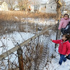 Peabody:<br /> Amy Carrion holds her daughter, Gabriella, 11 months, and her other daughter, Alyza, 3 1/2, stands near her in front of the abandoned lot next to their home on Seawall Street in Peabody.<br /> Photo by Ken Yuszkus/Salem,  News, Thursday,  December 23, 2010.