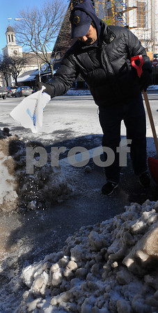 Beverly:<br /> Madhu Rane sprinkles some ice melting granules onto the sidewalk in front of the Beverly Market on Cabot Street to melt the ice covered walkway. The ongoing cold has preserved the snow piles since the snowfall from sunday. The forecast of more cold weather will keep the frozen snow around a few more days. <br /> Photo by Ken Yuszkus/Salem News, Wednesday,  January 14, 2009.