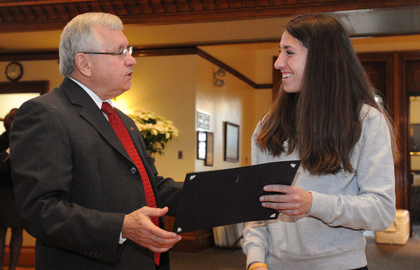 Peabody:<br /> Mayor Bonfanti gives a citation to runner Catarina Rocha. Runner Nick Christensen received one too. Also, he honored the state champion girls soccer team and gave out citations to them at Peabody City Hall Thursday morning.<br /> Photo by Ken Yuszkus/Salem News, Thursday, December 15, 2011.