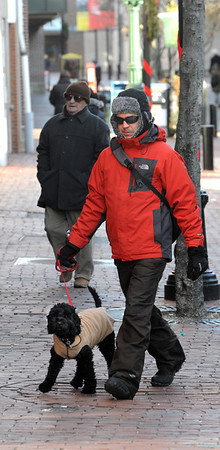 Salem:<br /> Humberto Tavares walks his client's dog, Walter, who is wearing a sweater. They are both keeping warm despite the wind and cold while out for a walk on Essex Street.<br /> Photo by Ken Yuszkus/Salem News, Wednesday, January 4, 2011.