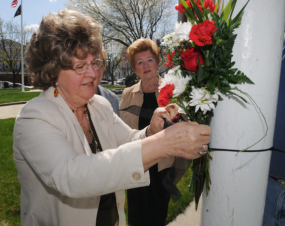 Peabody:<br /> From left, Lola Busta, president of the United Polish Organization, attaches a bouquet of flowers to the flag pole infront of the Peabody City Hall as Emila Zastrowski, hidden, and Helen Bielawa, both representatives of the United Polish Organization, watch the ceremony to lower the flag to half mast.<br /> Photo by Ken Yuszkus/Salem News, Monday, April 12, 2010.