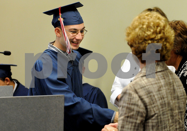 Salem:<br /> John Love receives his diploma . He is graduating from the Embark Program during the graduation ceremony at Salem State College Enterprise Center.<br /> Photo by Ken Yuszkus/Salem News, Tuesday, June 16, 2009.