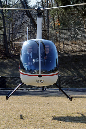 Danvers:<br /> St. John's Prep, senior Erik Slettehaugh, left, of Groveland, pilots a helicopter over the Cronin Stadium field at St. John's Prep school where he eventually landed. Chris Ramsey, flight instructor, is on the right.<br /> Photo by Ken Yuszkus/Salem News, March 10, 2010.