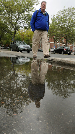 Salem:<br /> Parker Wilde, of Marblehead, walks on Lafayette Street in Salem. His reflection follows along in the rain puddle created by the recent rains.<br /> Photo by Ken Yuszkus/Salem News, Thursday, May 10, 2012.