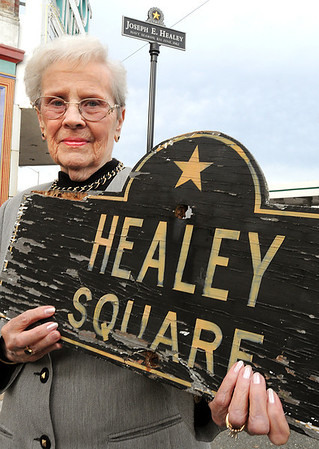 Beverly:<br /> Lois Healey is the widow of Frederick Healey, a veteran for whom Healey Square was named in 1976. On Veterans Day this year the city mistakenly rededicated the square in honor of another veteran, Joseph Healey. The city has ackowledged its mistake and plans to put up a new sign in honor of Frederick Healey. Mrs. Healey is holding the old Healey Square sign in honor of her husband. The newer Joseph Healey sign is in the background.<br /> Photo by Ken Yuszkus/Salem News, Monday, November 28, 2011.