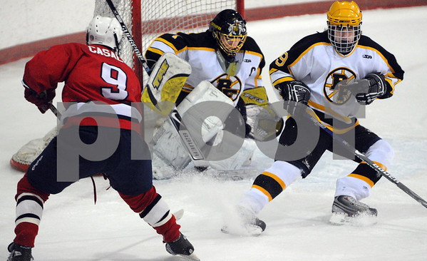 Peabody:<br /> Bishop Fenwick's goalie Craig Forrest catches the puck in his glove which was shot by Lynn's #9 Dan Casale, left, as Bishop Fenwick's #9 Andrew Ruby defends the goal during the Lynn vs Bishop Fenwick hockey game at McVann-O'Keefe Rink.<br /> Photo by Ken Yuszkus/Salem News, Friday,  February 20, 2009