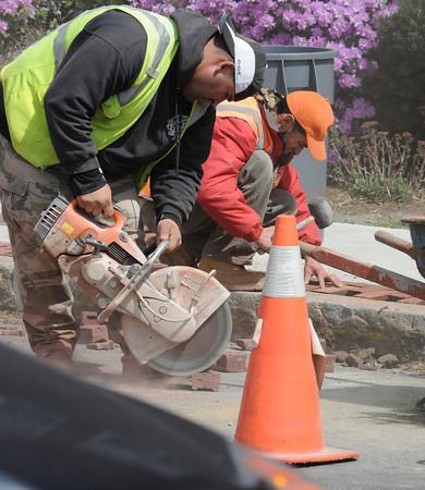 Salem:<br /> Andre Benjamin, left, and Francisco Carreiro work on cutting and placing blocks along the sidewalks on Bridge Street.<br /> Photo by Ken Yuszkus/Salem News, Tuesday, April 10, 2012.