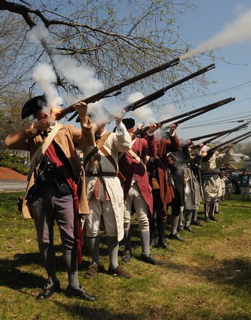 Danvers:<br /> The Danvers Alarm List Company, a group of Revolutionary War re-enactors, fire a musket salute after a wreath was laid at the foot of the memorial to Danvers residents slain at the battle of Lexington in 1775. The site is where  Capt. Israel Hutchinson lived, and there is now a memorial marker there, erected in 1896.<br /> Photo by Ken Yuszkus/Salem News, Monday, April 16, 2012.