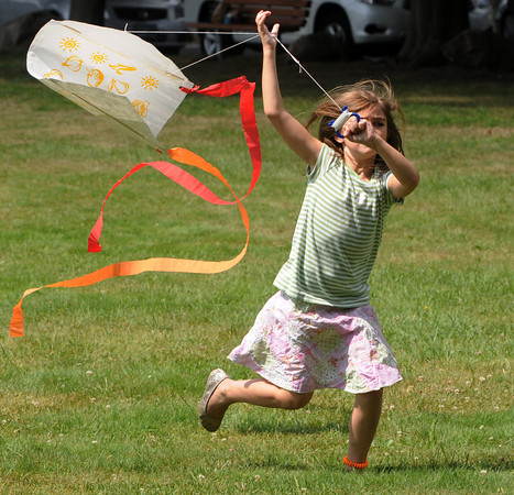 Peabody:<br /> Cecelia Pellizzaro, 6, of Peabody, runs to get her new kite to fly at the end of summer celebration held at Emerson Park. The Peabody Institute Library, Main Branch hosted a free picnic lunch with kites given to the children before a talk and demonstration by Todd Brodeur, 2-Time Freestyle Frisbee World Champion. <br /> Photo by Ken Yuszkus/The Salem News, Wednesday, August 22, 2012.