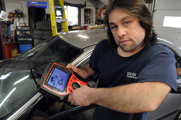 Salem:<br /> Jim Sully, of SS Automotive, holds a scanner whch is plugged into an automobile at the garage.<br /> Photo by Ken Yuszkus/Salem News, Thursday, March 4, 2010.