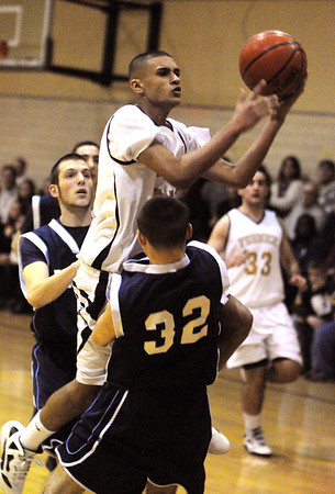 Peabody:<br /> Bishop Fenwick's Rishad Khan De Silva knocks down Peabody's Stephen Girolamo while going for a basket during the Peabody at Bishop Fenwick boys basketball game.<br /> Photo by Ken Yuszkus/Salem News, Tuesday, December 27, 2011.