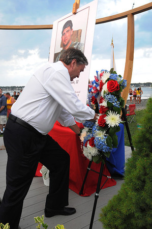 Salem:<br /> John Tierney, D-Salem places the wreath on the stage for the tribute of U. S. Army Sgt. James Anthony Ayube II Monday evening at Derby Wharf.<br /> Photo by Ken Yuszkus/Salem News, Monday, July 4, 2011.