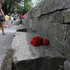Salem:<br /> People walk by the red carnations placed at the stone memorial with Susannah Martin's name which is part of the Salem witch trials memorial. She was hanged as a witch in 1692. <br /> Photo by Ken Yuszkus/The Salem News, Friday, August 10, 2012.