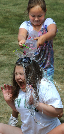 Beverly:<br /> Serena Hayden has a cup of water poured on her head by Annamarie Kozlowski during a playground activity at Balch Street playground. They are playing Agua Menti, which is a variation of the Duck, Duck, Goose game, but has a Harry Potter theme.<br /> Photo by Ken Yuszkus/Salem News, Wednesday, July 13, 2011.