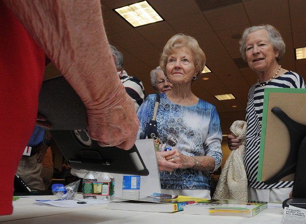Peabody:<br /> Theresa Murphy, left, resident and Paule Lambert, visitor, listen to the presentation on how to use the Apple ipad, pictured on the far left, during the Brooksby Village technology expo. <br /> Photo by Ken Yuszkus/Salem News, Thursday, June 28,  2012.