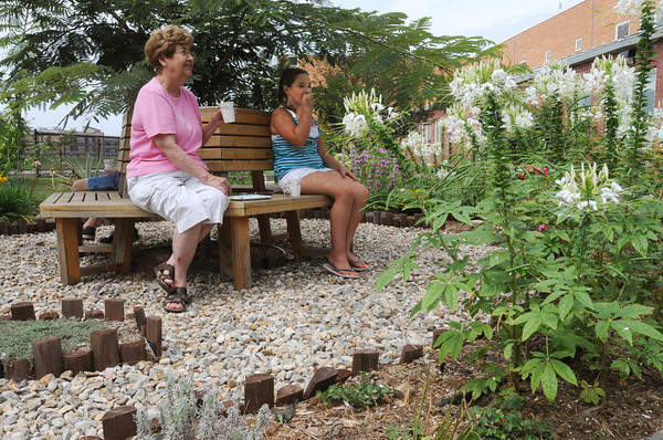 Salem:<br /> Eileen Dube and her granddaughter, Sara Eddy, who is a garden member, eat lunch in the garden created at the Nathaniel Bowditch School over the past 3 years. The lunch is a garden celebration for the end of summer school.<br /> Photo by Ken Yuszkus/The Salem News, Friday, August 10, 2012.