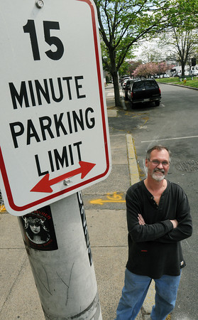 Salem:<br /> Michael Szczuka stands near the current parking sign in front of his business, Essex Cleaners. The city plans to install parking meters in front of Essex Cleaners, which has always had 15 minute stop-and-go parking spaces in front of it.<br /> Photo by Ken Yuszkus/Salem News, Thursday, April 26, 2012.