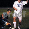 Danvers:<br /> Jared Shields of Peabody reaches for the soccer ball with one knee down on the ground as he combats Cameron Barrett of Danvers at the Peabody vs Danvers boys soccer game at Danvers High School.<br /> Photo by Ken Yuszkus/Salem News, Tuesday September 23, 2008.