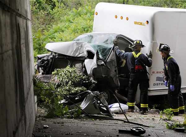 Peabody:<br /> Peabody firefighters survey the damage to the truck which crashed into a bridge abutment at the Route 95 north and Route 128 split on Monday morning.<br /> Photo by Ken Yuszkus/Salem News, Monday, June 13, 2011.