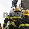 Beverly:<br /> Roberto Yapor crawled off the peek of the roof of the United Methodist Church onto the firetruck's ladder. Many onlookers watched as police and fire personel attempted to get him down. Danvers firefighters Craig Vesey and David Mondi climb the ladder to grab Roberto Yapor  because he appeared to be climbing over the ladder.<br /> Photo by Ken Yuszkus/Salem News, Monday October 6, 2008.