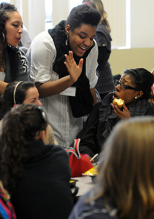 Salem:<br /> From left, Tamara Efstratios, a 2010 graduate who is currently enrolled at Regis College, and Christina Berthaud, a 2009 graduate who is currently enrolled at St. John's University, talk with Ashley Saint Louis, a senior, in the Salem Academy Charter School cafeteria. Salem Academy Charter School hosted an Alumni Event on Thursday. Returning graduates hosted a panel for 11th and 12th grade students, who got a chance to ask questions of the graduates about what they have been doing since they've graduated.<br /> Photo by Ken Yuszkus/Salem News, Thursday, January 6, 2011.