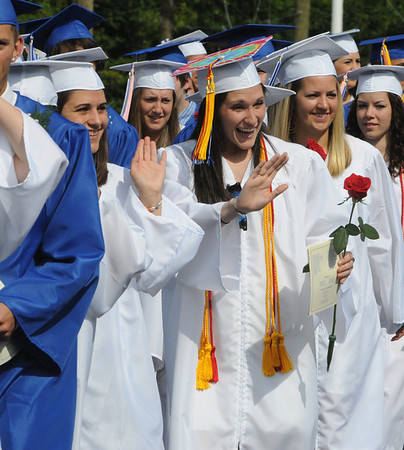 Danvers:<br /> Graduates wave to the crowd as they march past the bleachers during the processional of the Danvers High School graduation at Dr. Deering Stadium. <br /> Photo by Ken Yuszkus/Salem News, Monday, June 13, 2011.