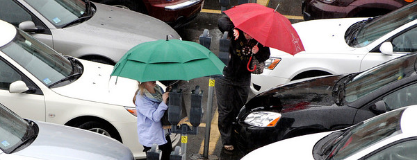 Salem:<br /> While holding their umbrellas, two ladies attend to their parking meters in the pouring rain at the parking lot on Church Street in Salem.<br /> Photo by Ken Yuszkus/Salem News, Wednesday, April 13, 2011.