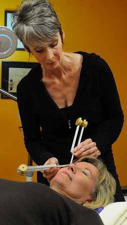Beverly:<br /> Sally Amore uses tuning forks during a technique to tone and lift the muscles of the face of Suzanne Drinkwater.<br /> Photo by Ken Yuszkus/Salem News, Thursday November 19, 2009.