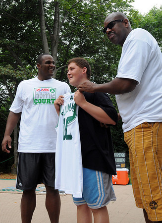 """Salem:<br /> Celtics Glen """"Big Baby"""" Davis, left, and former Celtics Cedric Maxwell, present a Celtics jersey with the name Plummer printed on it, to Patrick Lee, center, who accepted it for the Plummer Home for Boys. Glen """"Big Baby"""" Davis and Cedric Maxwell were at the Plummer Home for Boys for the dedication of the basketball court that the Celtics helped build along with the NFL quarterback Steve Young's Foundation. They also shot a few hoops with the kids.<br /> Photo by Ken Yuszkus/Salem News, Monday August 16, 2010."""