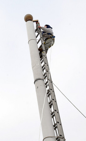Salem:<br /> Joshua Levesque, is at the top of a ladder to replace the rope on the flagpole on the roof of the Hawthorne Hotel.<br /> Photo by Ken Yuszkus/Salem News, Thursday, December 24, 2009.