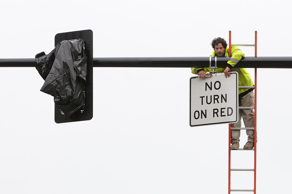 "Salem:<br /> John Whalen installs a ""No turn on red"" sign on the horizontal metal pipe holding the new traffic lights which will be soon be working at the corner of Derby Street, Hawthorne Boulivard, and Congress Street.<br /> Photo by Ken Yuszkus/Salem News, Monday, May 16, 2011."