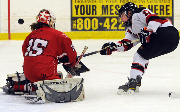 Salem:<br /> Masconomet's goalie Alex Jones, left, blocks as Marblehead's Brittany Smith shoots the puck. It goes high and misses the net during the Marblehead vs. Masconomet girls hockey at Salem State's hockey rink.<br /> Photo by Ken Yuszkus/Salem News, Tuesday, December 27, 2011.