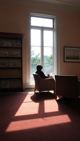 Beverly:<br /> The sunlight streams through a window onto a woman reading near a window at the Beverly Public Library.<br /> Photo by Ken Yuszkus/Salem News, Wednesday,  September 8, 2010.