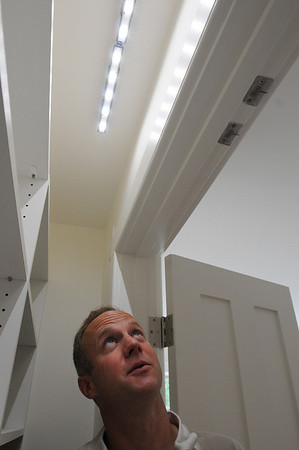 "Beverly:<br /> Jim Farnham looks upward toward some of the LED lights in a closet which are activated by a sensor in the house at 6 Beaver Pond Road in Beverly. A local company called Cleantech Homes opened the newly constructed ""ultra-sustainable home"" which they are using as an  information and learning center for sustainable building practices.<br /> Photo by Ken Yuszkus/Salem News, Thursday August 12, 2010."