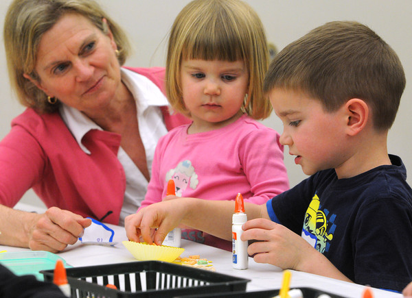 Hamilton:<br /> Grandmother Susan Rich, left, and Grace Rich, 3, watch as Ben Rich, 5, creates a paper lion out of construction paper, paper cupcake forms, cereal, string, and glue at the Hamilton-Wenham Public Library's Rhythm and Rhyme story class. Lions were the theme of the books read that day.<br /> Photo by Ken Yuszkus/Salem News, Tuesday, May 15, 2012.