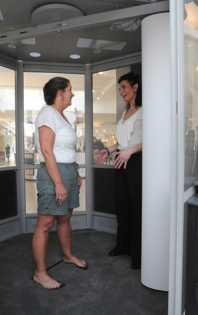 Peabody:<br /> Paula MacLeod, left, stands inside the Me-ality booth as Victoria Messina, manager, explains the scanning process at the North Shore Mall. The Me-ality booth lets women size their jeans by having their body scanned for measurements.<br /> Photo by Ken Yuszkus/Salem News, Thursday,  March 22, 2012.