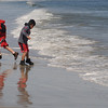 Ipswich:<br /> Ivan Demarjian,8, of Gloucester, left, and Michael Quill,8, of Essex, run from the incoming waves at Crane Beach. It was a free family fun day at Crane Beach on Monday. Besides the free admission, there were activities for all ages during the day.<br /> Photo by Ken Yuszkus/Salem News, Monday, April 18, 2011.