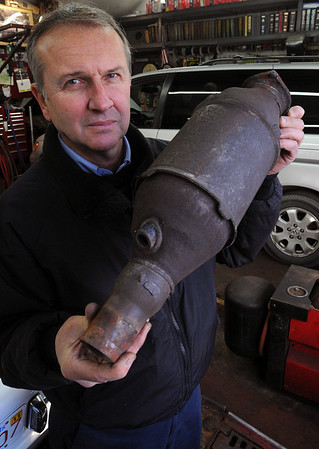 Salem:<br /> Ray Collins, one of two partners that own the North Shore Auto Clinic, holds up a catalytic converter that was removed from a Jeep Cherokee.<br /> Photo by Ken Yuszkus/Salem News, Wednesday, December 16, 2009.