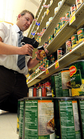 Salem:<br /> Mike Atkinson, grocery manager, applies price tags to cans of corn at Crosby's grocery store. The cans have to be removed from the shelf before they can be tagged.<br /> Photo by Ken Yuszkus/Salem News, Friday, May 21, 2010.