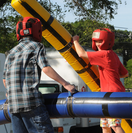 Danvers:<br /> Cale Cornichuk, left, braces as he is hammered by his brother Dorian while playing the Pedestal Joust game at Plains Park early evening before the start of the fireworks.<br /> Photo by Ken Yuszkus/Salem News, Tuesday, July 3,  2012.