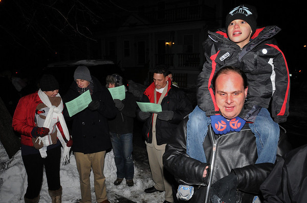 Beverly:<br /> Eddie Hoke of Beverly holds Gage Windsor,7, of Salem, on his shoulders while they sing Christmas carols with the group in the Gloucester Crossing neighborhood.<br /> Photo by Ken Yuszkus/Salem News, Tuesday, December 22, 2009.